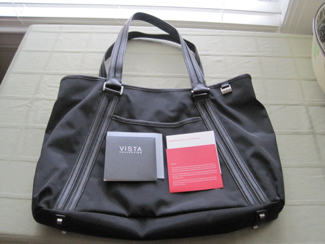 This is a black nylon handbag made by Tumi in the Vista...